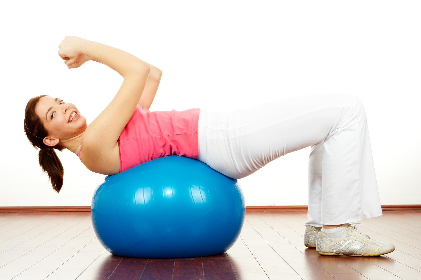 Fiatal lány gyakorlatot végez egy gumi labdán