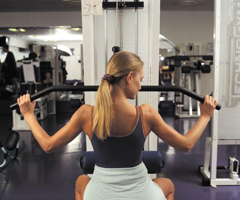 Fitness teremben egy hölgy edz