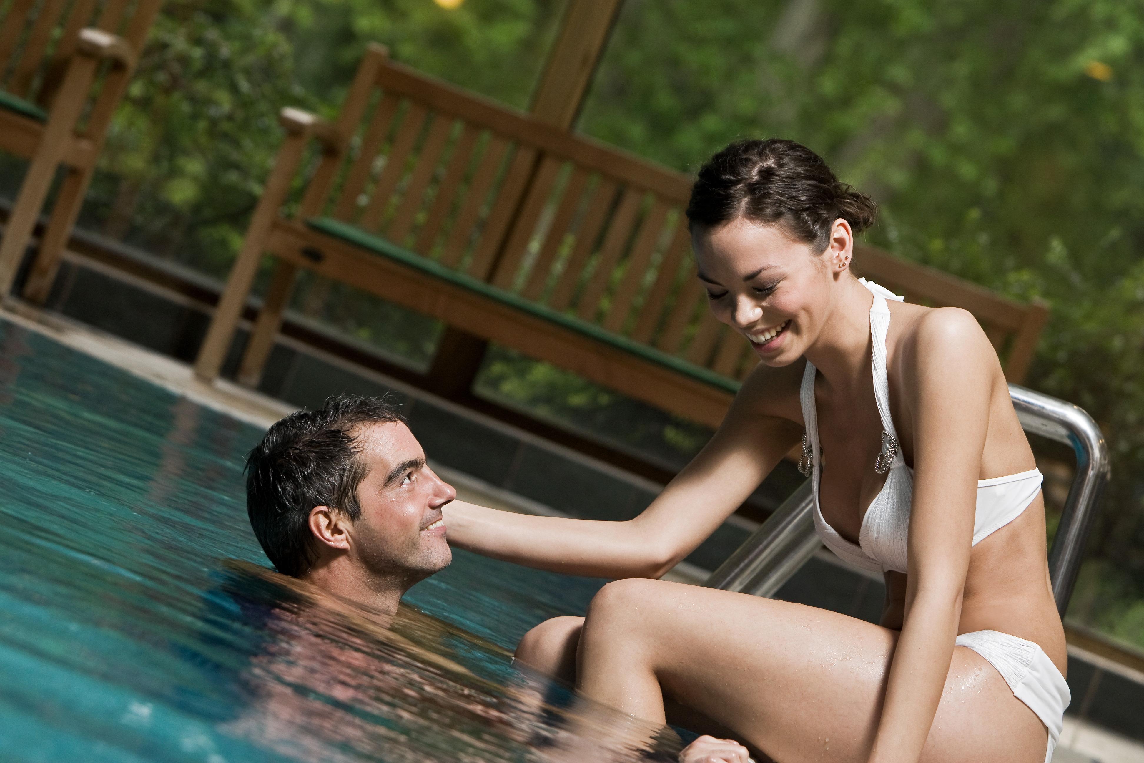 Medence szélén ülő lány, vízben fürdőző férfi