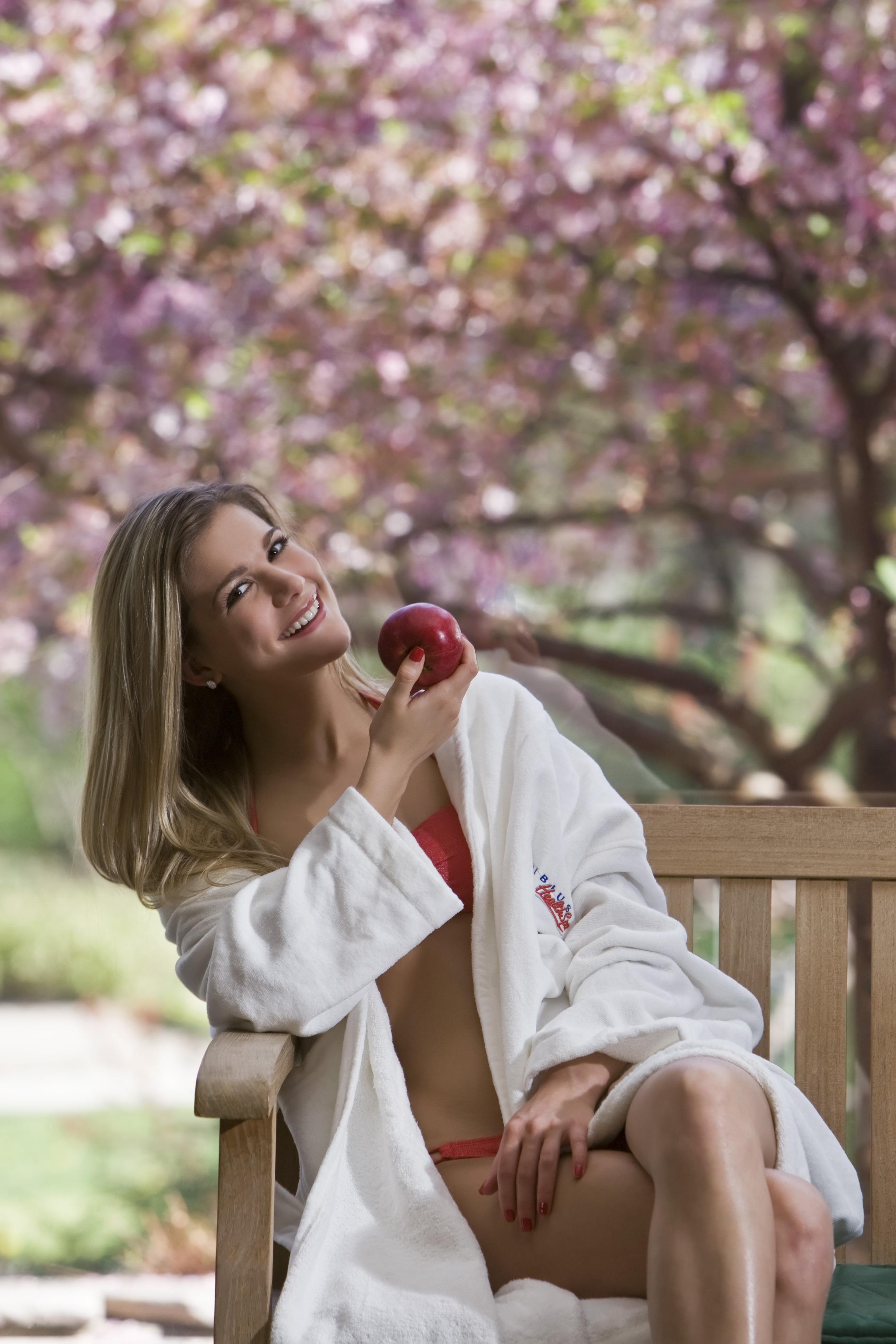 Virágos fa alatt almát eszik a nő